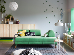 A modern living room with FLOTTEBO sofa-bed in green with side table in the centre of the room.