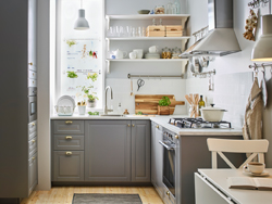 A small sized, traditional-style gray and white kitchen with BODBYN drawer fronts in grey and brass-color ENERYDA knobs and cup handles.