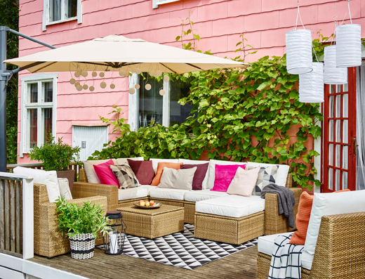 SOLLERÖN corner sofa, armchair and footstool in brown and white KUNGSÖ cushions arranged on an outdoor terrace under a large parasol in front of a pink house.