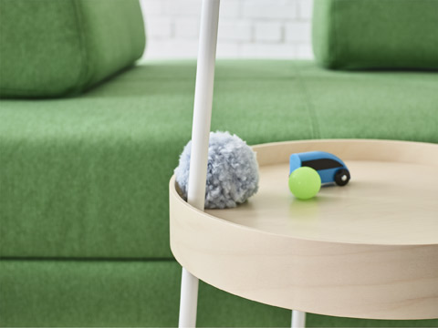 The flexible IKEA BURVIK side table can be moved around with one hand without things falling off.