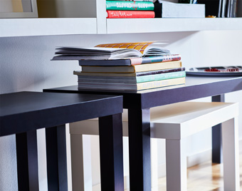 Nesting tables, a bigger black cradling a smaller white, are easily swept to the side when not in use – and even then they're useful.