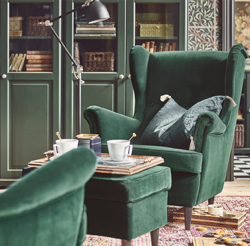 The unmistakable shape of a STRANDMON wing chair, complete with a matching, dark green footstool – offering relaxation enveloped in style.