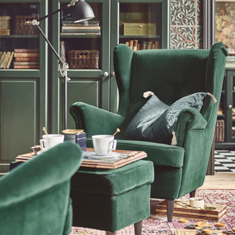 The unmistakable shape of a STRANDMON wing chair, complete with a matching, dark green footstool. Chosen here to represent IKEA sofas and armchairs that are as elegant as they are comfortable.