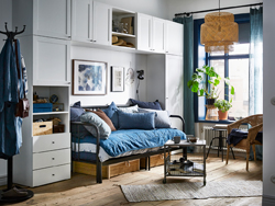 A blue and white studio apartment with the white PLATSA wardrobe arranged around a sleeping / living room zone.