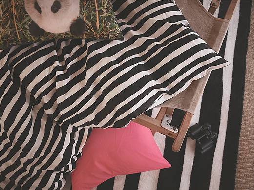 URSKOG quilt cover in black and white stripe laying over an orange pillow