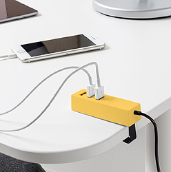 A mobile phone attached to a USB charger, both placed on a white table.