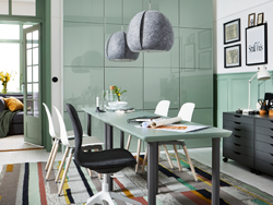 A green and gray home office space with ÅMLIDEN/ALVARET in gray-green/gray table in the center and closed gray-green storage behind.