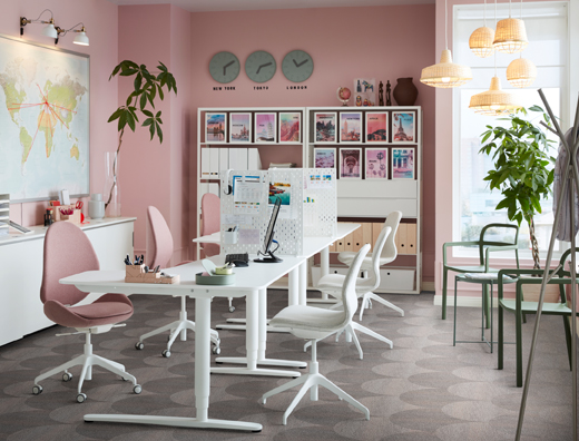 An office space with pink walls and sit/stand BEKANT desk in white and ergonomic HATTEFJÄLL swivel chairs in light brown-pink.