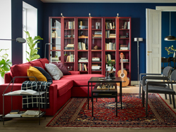 A black, red and blue living room with the comfortable KIVIK 3-seat sofa with chaise lounge in red placed by the windows.