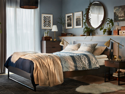 A cosy, modern bedroom in blue and brown with a TRYSIL bed, bedside table and chest of 4 drawers in dark brown.