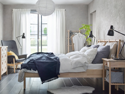 A beige and grey bedroom with BJÖRKSNÄS bed, bedside table and chest of 5 drawers made from solid birch wood.