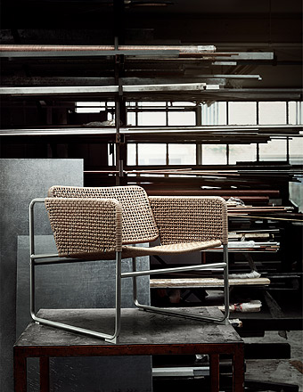 The INDUSTRIELL armchair has a frame in grey steel and seat and backrest in hand-woven paper fibre in a natural brown colour.