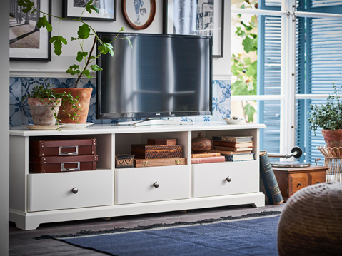 The white TV bench with plinth rail and traditional details has both open shelves and drawers.