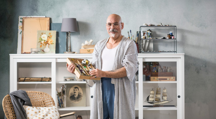 Bald male painter holding a box of paint tubes, standing proudly in front of his paint collection together with pieces of SAMMANHANG.