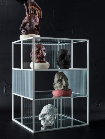 SAMMANHANG glass shelf filled with different sculptures against black backdrop.