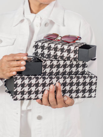 Close up of hands holding patterned SAMMANHANG boxes with a pair of pink sunglasses on top