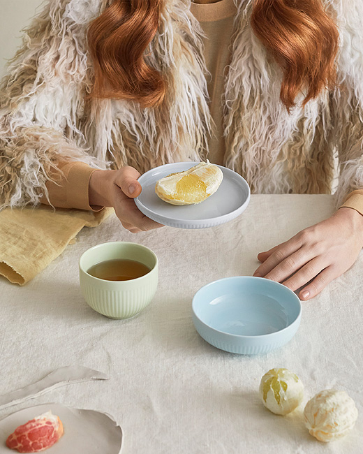 A red haired girl sits at a table holding a porcelain MORGONTE gray plate with an orange on it. Two different sized bowls from the same MORGONTE 3 piece set sit in front of her, one pastel blue and the other green along with oranges and part of a grapefruit.