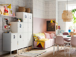 White HÄLLAN cabinets placed against a side wall and used for storage in a compact pink, white and yellow family living space.