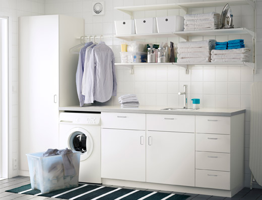 A laundry room with white wall shelves, base cabinets with doors or drawers and a high cabinet with shelves inside.