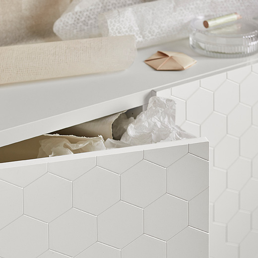 The BESTÅ system shown with the new VASSVIKEN door fronts with a hexagon pattern on a white background, which gives a modern three-dimensional effect.