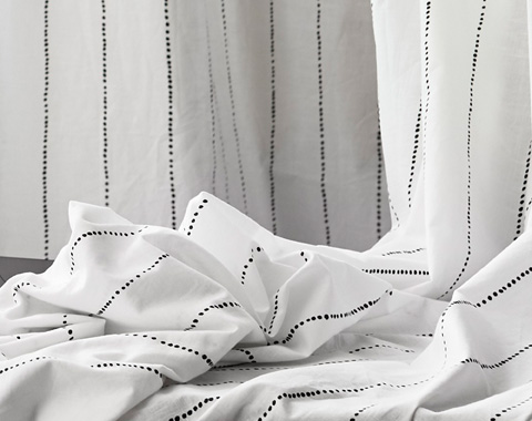 With a subtle pattern of dotted black lines on white, the 100% cotton EBBALISA curtain is easy to coordinate with thanks to its classic style.