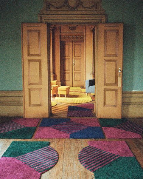 Modular green, purple and navy blue SJÄLVSTÄNDIG carpets in front of entrance to room with more carpets and STRANDMON furniture.