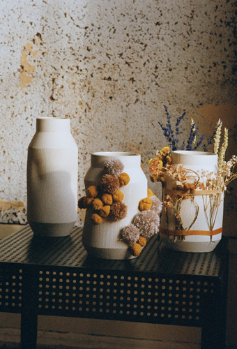 SJÄLVSTÄNDIG ceramic vases decorated with dried flowers and yarn accessories.