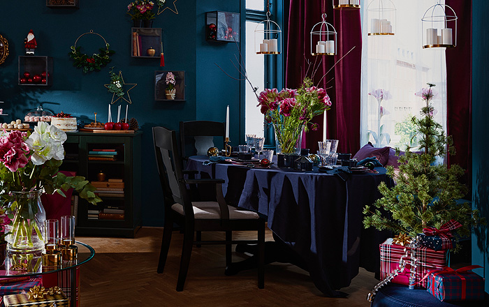 IKEA VINTER 2018 tablecloth in rich blue on a holiday set dining table in a room decorated for the holidays with greenery, floral arrangements and lighting.