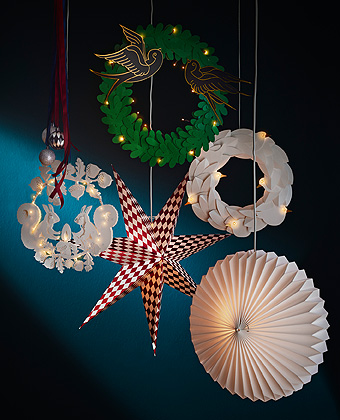 In the shapes of circles, hearts, angels, mushrooms, rabbits, birds, stars and squirrels, the STRÅLA holiday collection lighting hangs in a dark blue room.