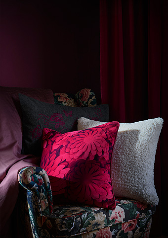 The IKEA VINTER 2018 Christmas cushions decorate a floral armchair in a dark red room.