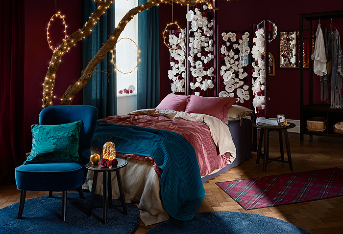 IKEA VINTER 2018 Christmas cushions decorate a holiday themed bedroom with dark blue and red textiles, string lights and floral decor.
