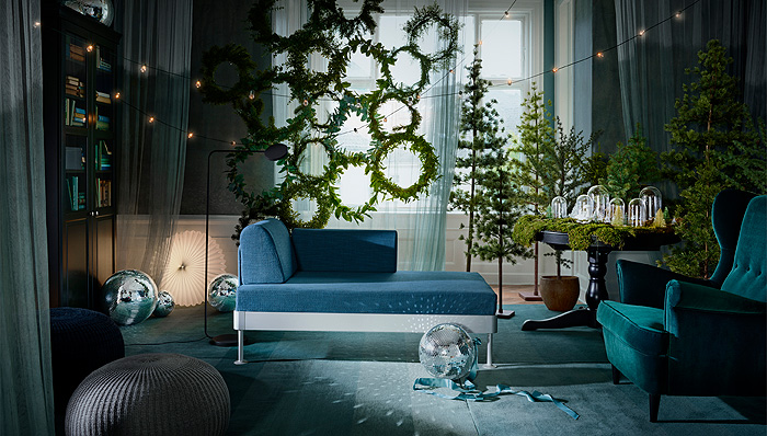 SMYCKA artificial Christmas wreaths hang in a dark blue and teal holiday decorated living room full of artificial greenery and string lighting.
