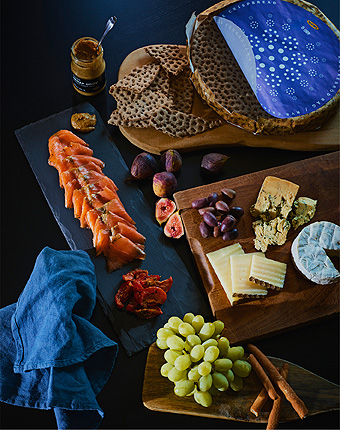 A Scandinavian platter with IKEA SJÖRAPPORT smoked salmon, crackers, cheeses, fruit and dips on a tabletop.