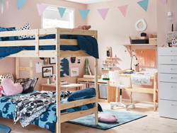 This child's pink bedroom walls are filled with hand drawn sketches and art. Nurture creativity with functional pine furniture that organises art supplies.