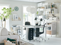 A green and grey home office space with ÅMLIDEN/ALVARET in grey-green/grey table in the centre and closed grey-green storage behind.