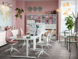 An office space with pink walls and sit/stand BEKANT desk in white and ergonomic HATTEFJÄLL swivel chairs in Gunnared light brown-pink.