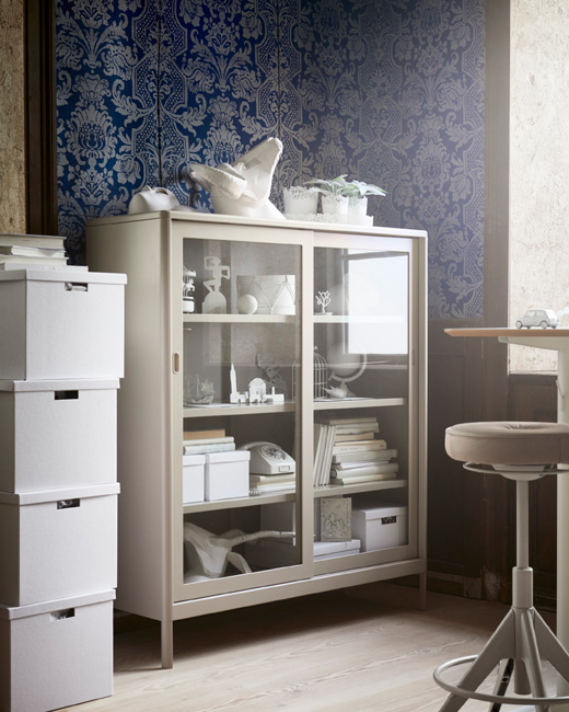 Add display and storage to your workspace using IDÅSEN cabinet with sliding glass doors. In beige steel, the industrial-styled cabinet from IKEA meets modern needs with room for cables behind its shelves.