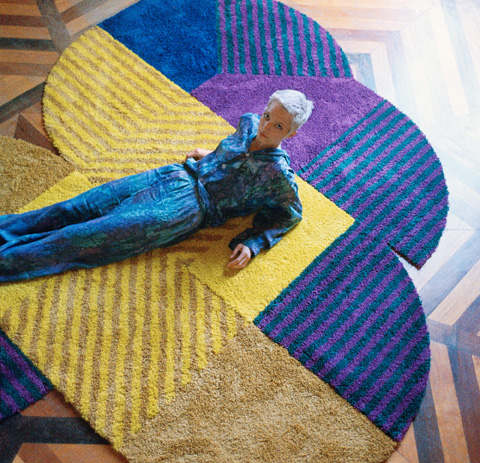Young female laying on blue, yellow and purple modular SJÄLVSTÄNDIG carpets.