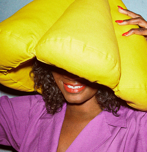 Close up of smiling female wearing the SJÄLVSTÄNDIG yellow, cone-shaped pillow as a hat.