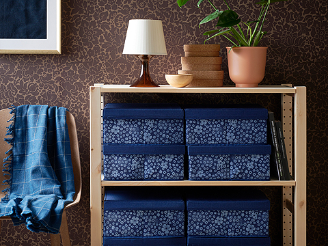 The IKEA STORSTABBE blue and white patterned floral boxes in polyester fabric can be stacked and look great on an open shelf.