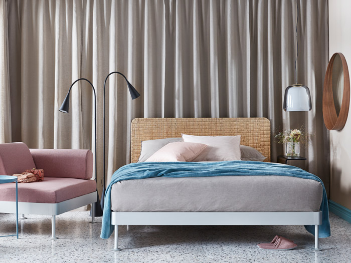 A bedroom that includes products from the DELAKTIG Collection, such as the bed frame, lamp, and sofa with armrest.