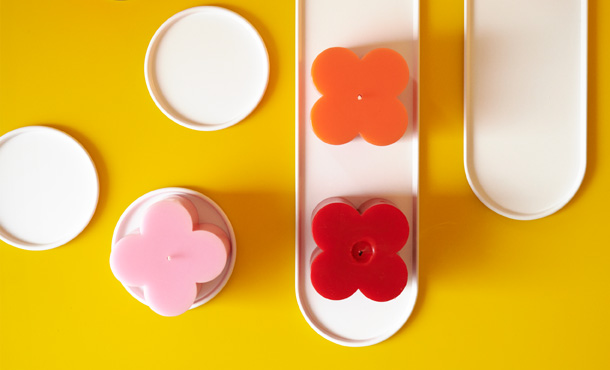 Some white, rounded IKEA SOMMAR 2019 candle dishes with flowery candles on display will immediately evoke summer feelings.