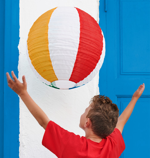A young boy with his arms outstretched catching a large colorfully striped paper lamp shade resembling a beach ball.