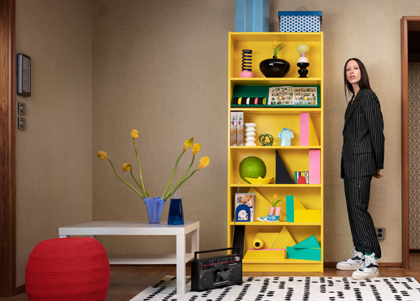 A woman standing next to a yellow bookcase with decorative items on it including vases and sculptures.