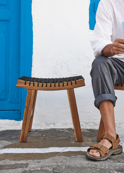 Close up of a brown wood acacia stool with a braided seat, and a partial shot of a man's leg sitting on another stool.