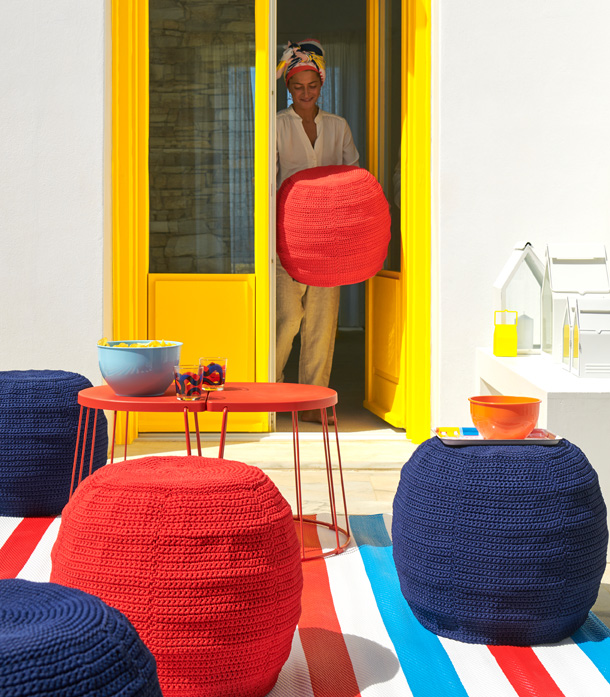 A red outdoor table with red and blue crocheted ottomans around it, and a woman in the back carrying one out from inside.