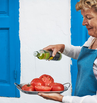 A woman with a blue apron holding a plate of tomatoes and pouring canola oil on them.