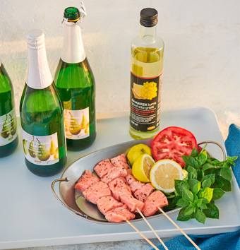 A tray with meat on skewers next to lemons and tomatoes, bottles of sparkling fruit drink, and a bottle of canola oil.