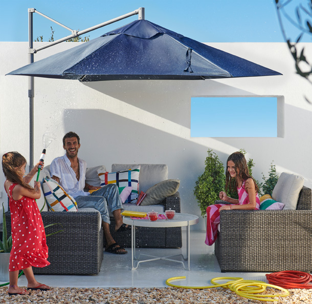 A man and two little girls playing under a large blue umbrella canopy with outdoor seating furniture under it.