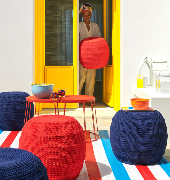 Red and blue footstools sitting outside around a table with a woman bringing another red footstool from inside.